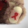 Detailansicht der gestickten AIDS-Schleife am Fuß des AIDS-Bären