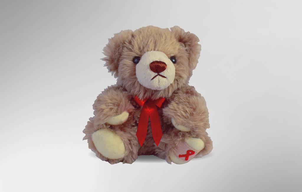 Plüschbär der AIDS-Stiftung von vorn. Sein Fell ist hellbraun, um den Hals trägt er eine rote Schleife und unter seinen linkem Fuß ist die AIDS-Schleife gestickt.