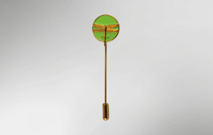 Goldene Stecknadel, an deren einem Ende sich ein grüner Kreis mit goldener Libelle befindet.