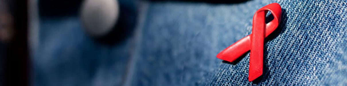 Bannerbild für den SHop: Aids-Schleife aus Metall als Anstecker auf Jeansstoff